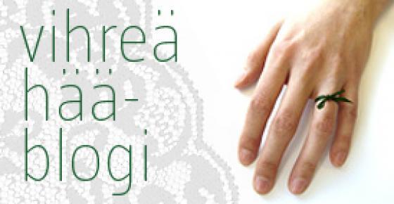 Käsi, jonka nimettömässä vihreä sormus.