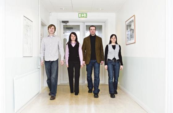 Neljä tutkijaa käytävällä.