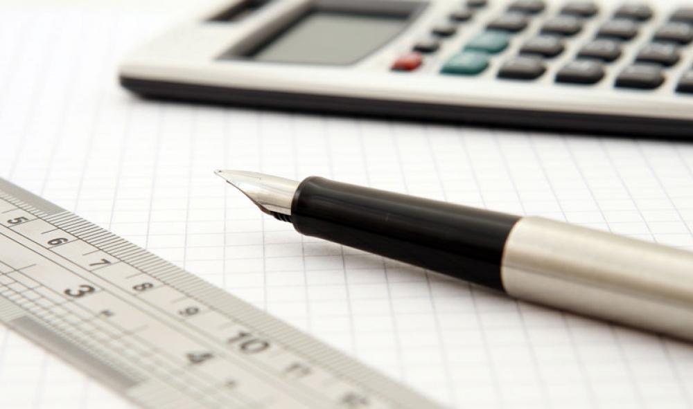 Kuvituskuvassa kynä ja laskin
