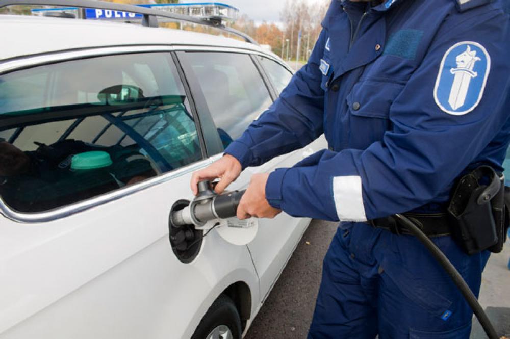 Poliisi tankkaa kaasua.