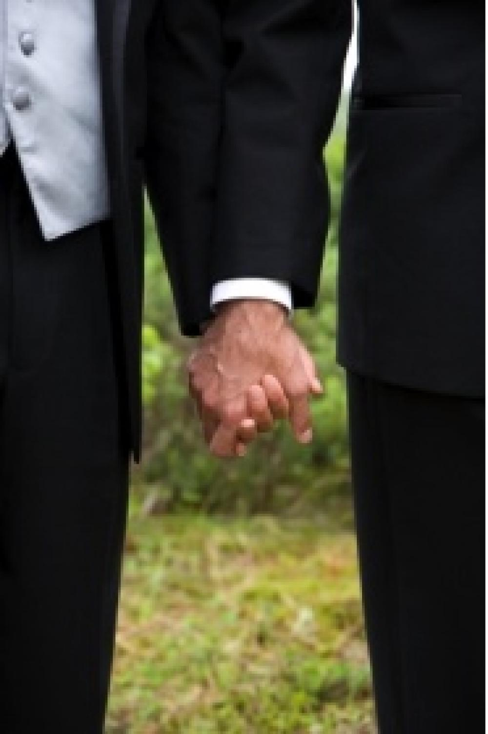 Frakkipukuinen miespari käsi kädessä