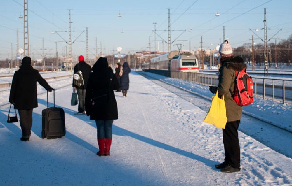 Ihmiset odottavat junaa pakkasessa.