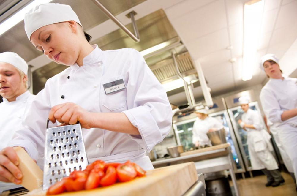 Kokkiopiskelija raastaa parmesaania